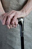 Hands of an elderly woman holding a cane. Close-up.
