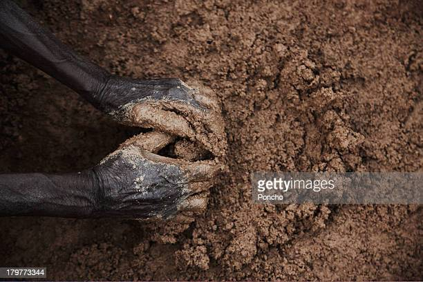 hands of an old man making mud for his hut