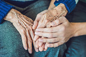 Hands of an old woman and a young man. Caring for the elderly. close up.