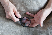 Hands of an old woman holding a magnifying glass. Close-up.