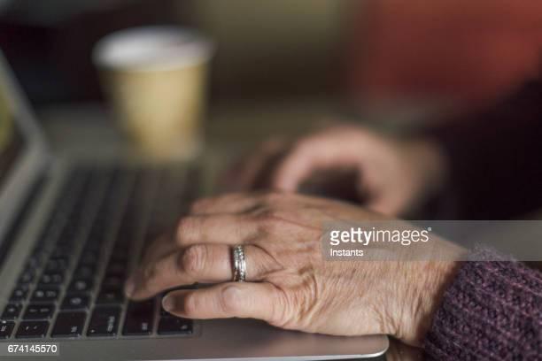 Hände eines unkenntlich 59 Jahre alte Frau, während sie auf einem Laptop in einem Café arbeitet.