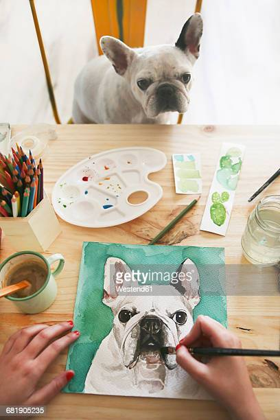 Hands of artist painting an aquarelle of her French bulldog