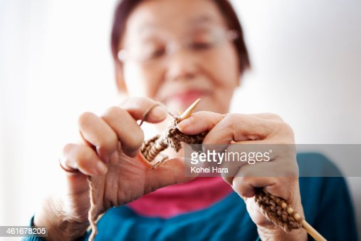 Hands of Asian old woman knitting