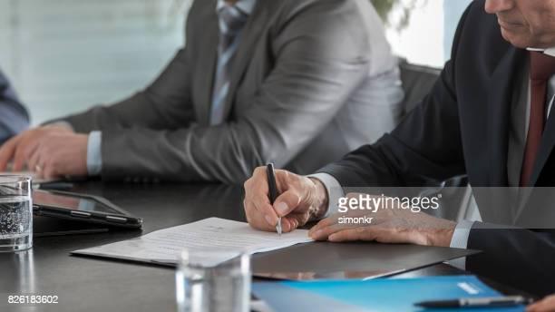 Händen der Geschäftsmann unterschreiben