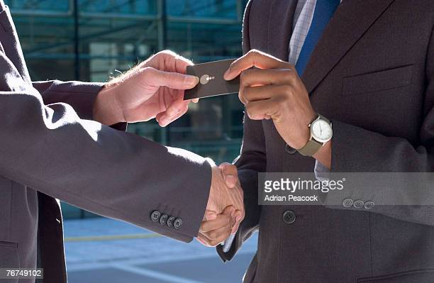 Hands of businessmen exchanging cards and shaking hands