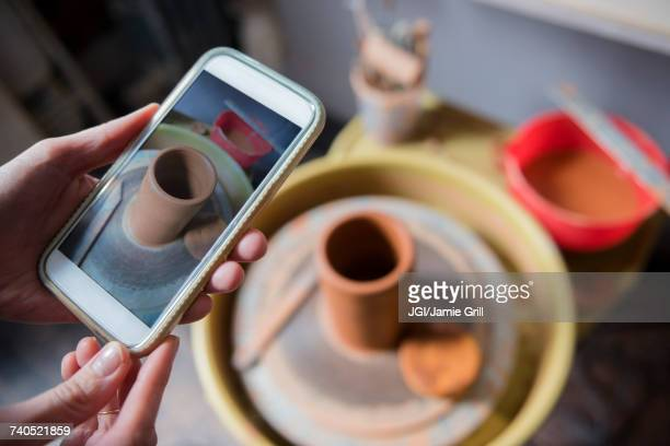 Hands of Caucasian woman photographing pottery with cell phone