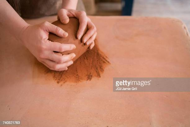 Hands of Caucasian woman rolling pottery clay