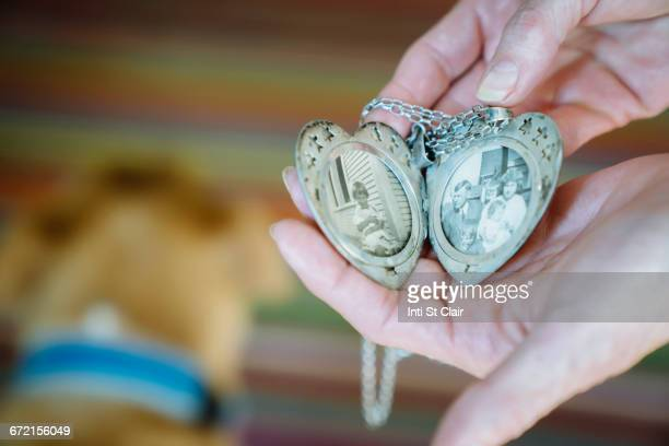 Hands of Caucasian woman showing photographs in cameo