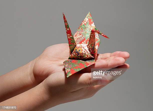 Hands of children carrying the origami.