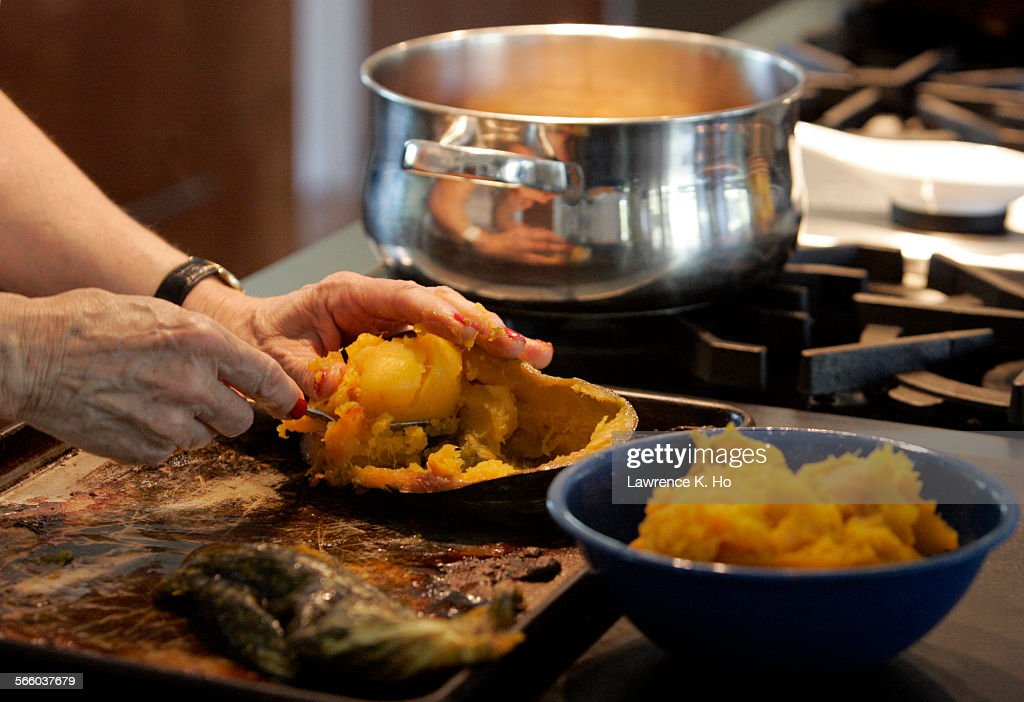 Hands of cookbook writer Anna Thomas scooping out the flesh of the Kabocha squash for the soup she is preparing for a dinner party at her home in...