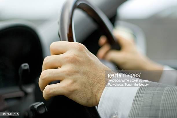 Hands of driver on steering wheel