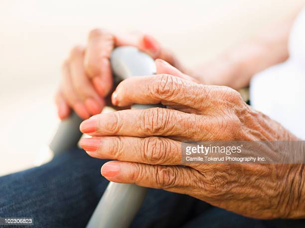 Hands of elderly woman holding a cane