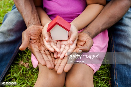 Hands of family together holding house in green park : Stock Photo
