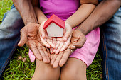 Hands of family together holding house in green park - family home and real estate concept