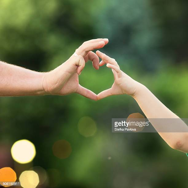 Hands of father and child forming heart