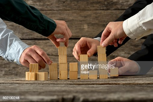 Hands of five businessman holding wooden blocks placing them int : Stock Photo