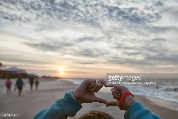 Hands of girl making heart shape on beach at sunrise
