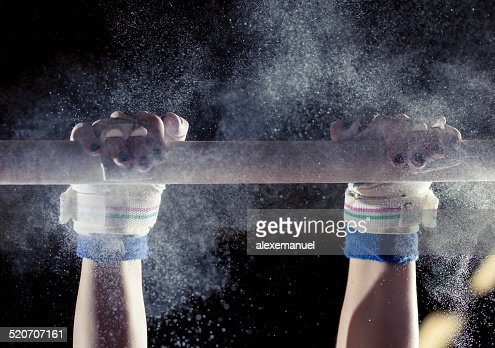 hands of gymnast with chalk on bars : Stock Photo