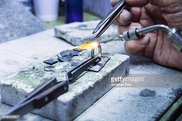 Hands of jewellery craftsman using miniature blowtorch on platinum ring