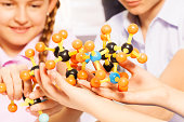Hands of young students assembling molecule models for science project