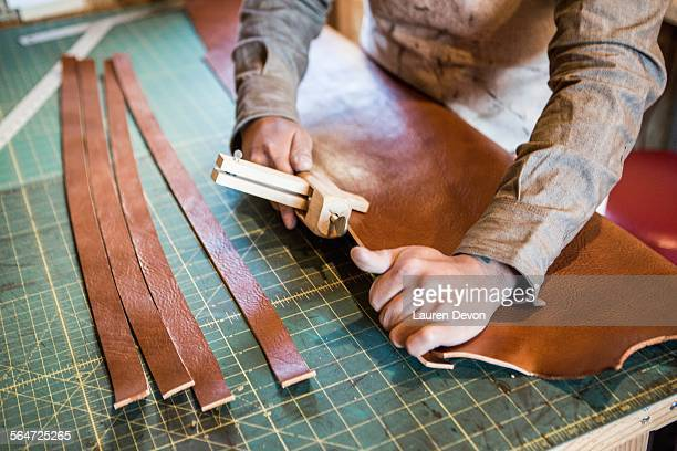 Hands of leather craftsman using wooden clamp on workshop bench