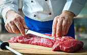 Hands of male chef in uniform cutting big piece of beef on board in restaurant kitchen. Man cuts meat with knife. Big piece of raw meat. Chef working in the kitchen