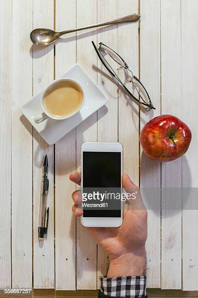 Hands of man with smartphone, cup of coffee, glasses, apple, spoon and pen