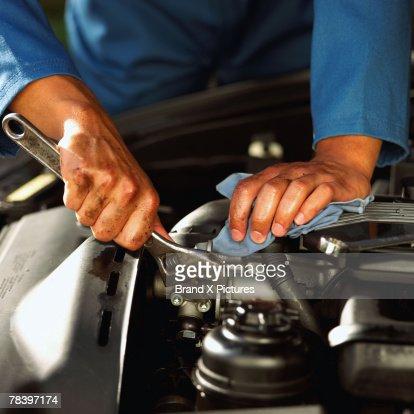 Hands of mechanic fixing engine : Stock Photo