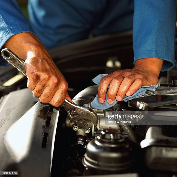Hands of mechanic fixing engine