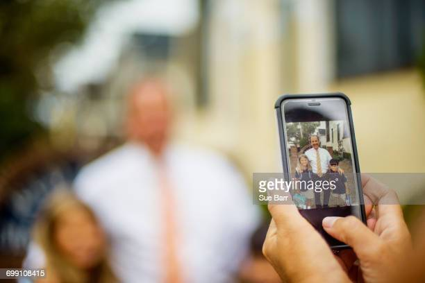 Hands of mother photographing male and female elementary school twins with father on smartphone