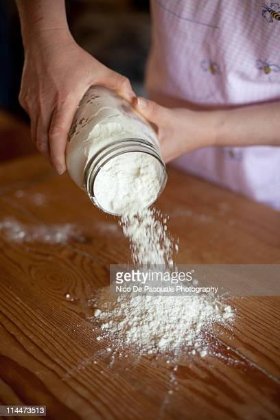 Hands of oman spilling some flour