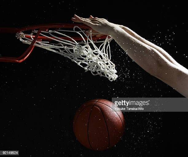 Hands of player slam dunking basketball into hoop