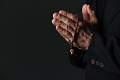 Hands of priest holding rosary and praying over black background