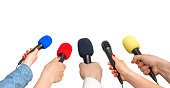 Hands of reporters with many microphones - journalism and broadcasting concept - isolated on white