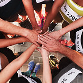 Hands of running team stacked on top of each other. Top view of a sports team standing in a circle with their hands stacked.