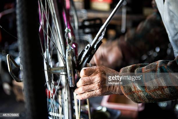 Hands of senior mechanic  repairing bicycle