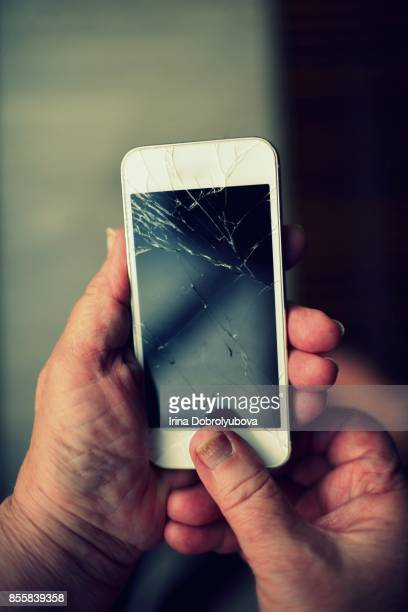 hands of senior woman holding broken smartphone