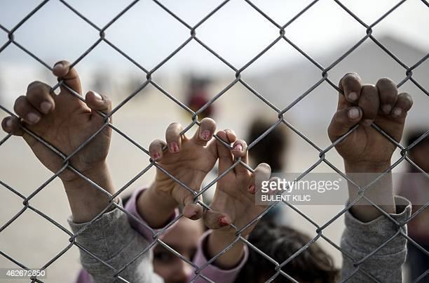 Hands of Syrian Kurdish children are seen holding a fence in a UNHCR refugee camp on February 2 at Suruc in Sanliurfa AFP PHOTO / BULENT KILIC