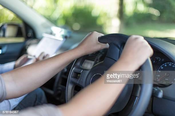 Hands of teenage girl at car steering wheel