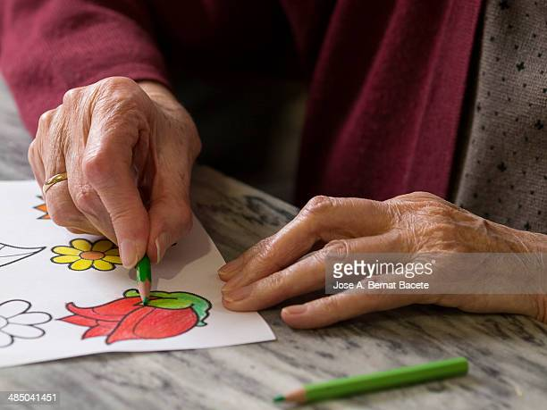 Hands of the elderly one doing with pencils