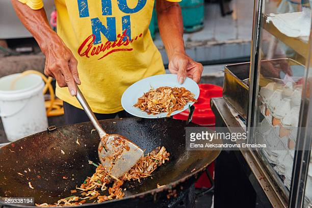 Hands of the senior man cooking kway teow noodles at the street market, Penang, Malaysia