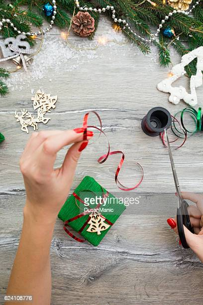 Hands of woman decorating Christmas gift box