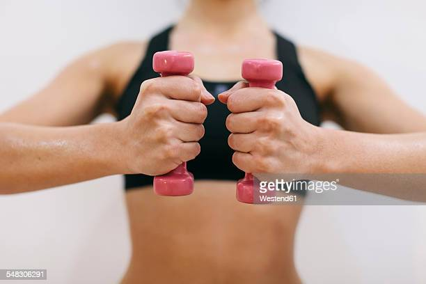Hands of woman holding dumbbells