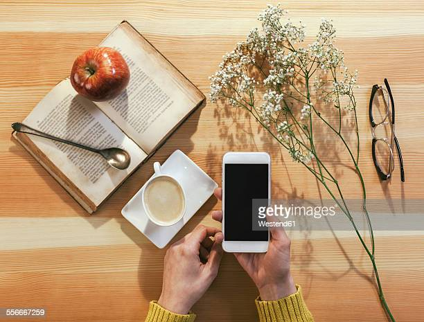 Hands of woman holding smartphone surrounded by other objects