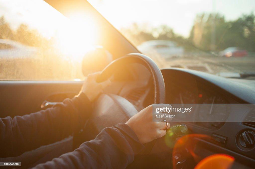 Hands of woman on car steering wheel