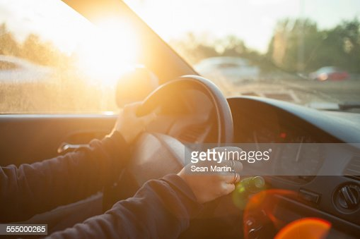 Hands of woman on car steering wheel
