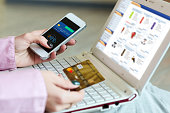Hands of Woman shopping on-line holding credit Card and Telephone making mobile Payment virtual Shop interface on white laptop