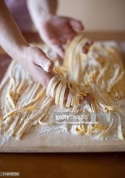 Hands of woman sorting some tagliatelle