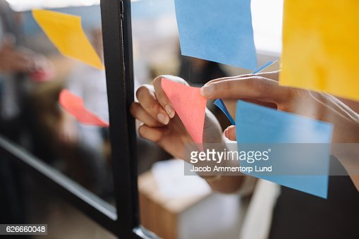 Hands of woman sticking adhesive notes on glass : Foto de stock