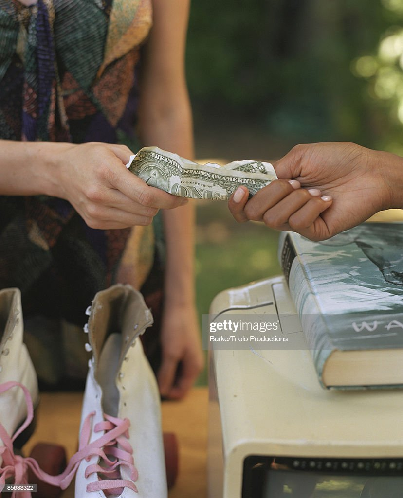 Hands of women exchanging cash for roller skates : Stock Photo